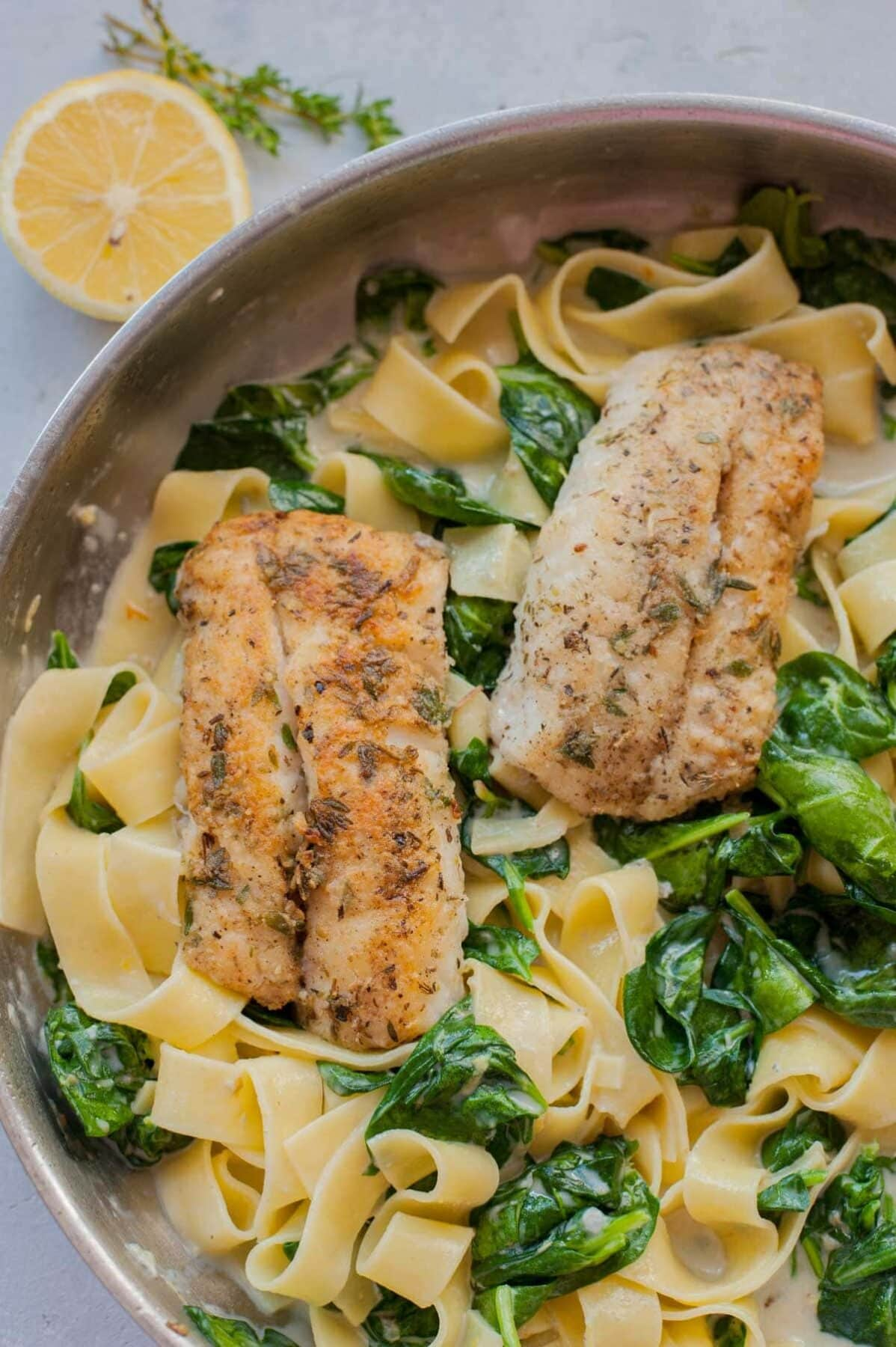Gorgonzola spinach pasta and pa-fried fish in a frying pan.