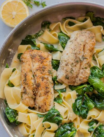 Gorgonzola spinach pasta with pan-fried fish in a frying pan.