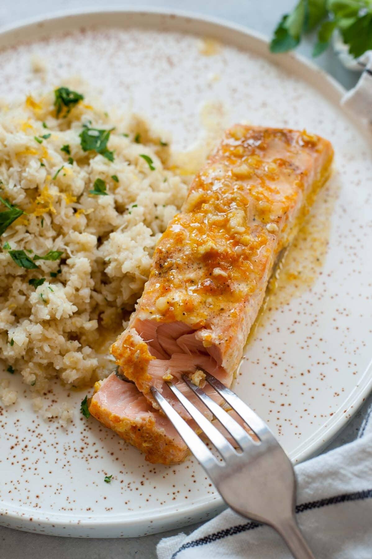 Filety z łososia w sosie pomarańczowym podane z ryżem z kalafiora na białym talerzu.