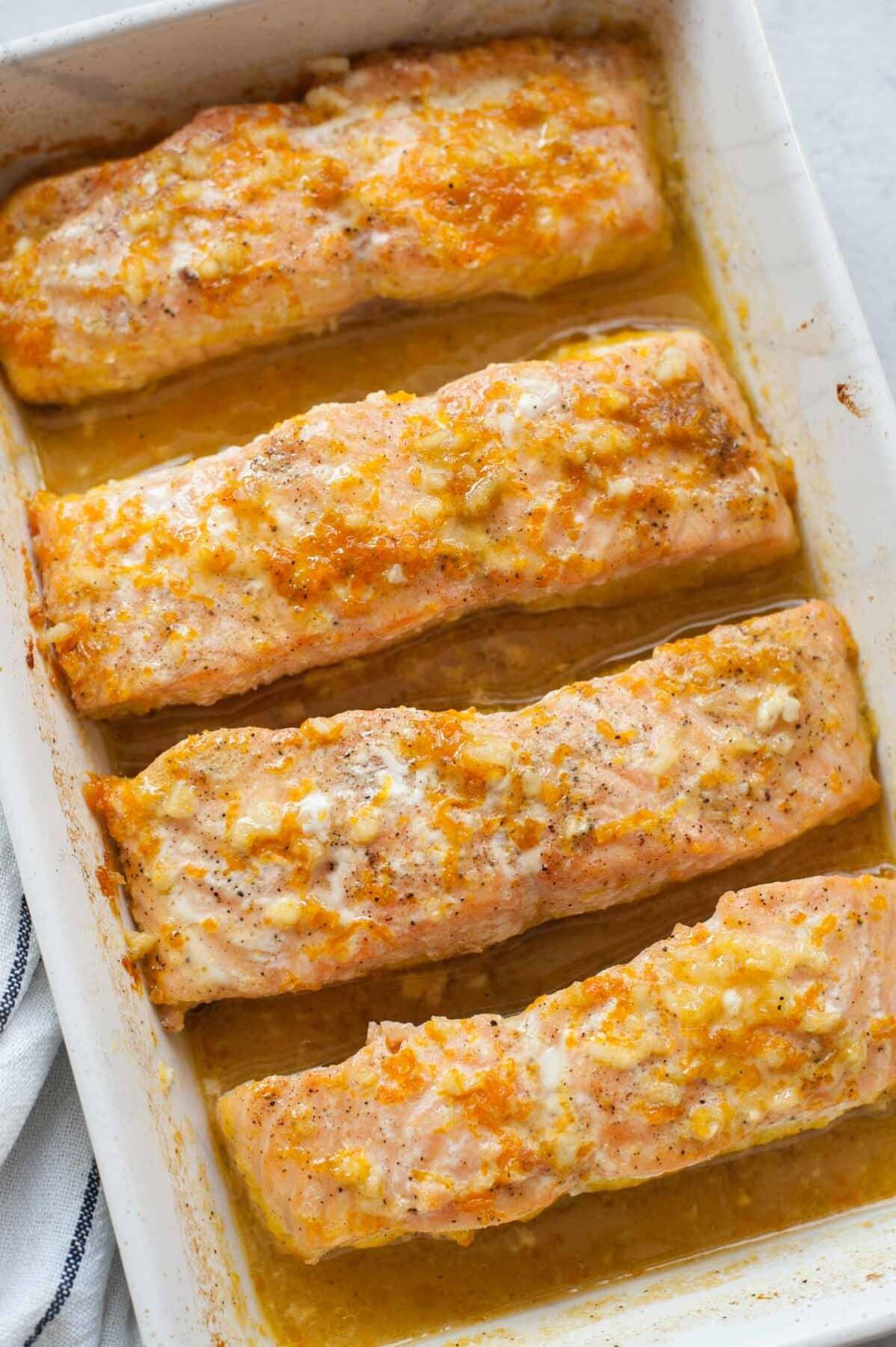 Filety z łososia w sosie pomarańczowym w białym naczyniu do zapiekania.