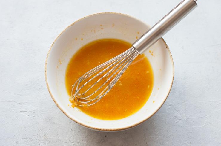 Biała miska z sosem pomarańczowym i trzepaczką.