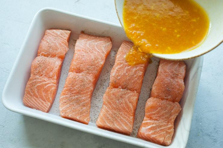 Sos pomarańczowy wlewany do białego naczynia do zapiekania z filetami z łososia.