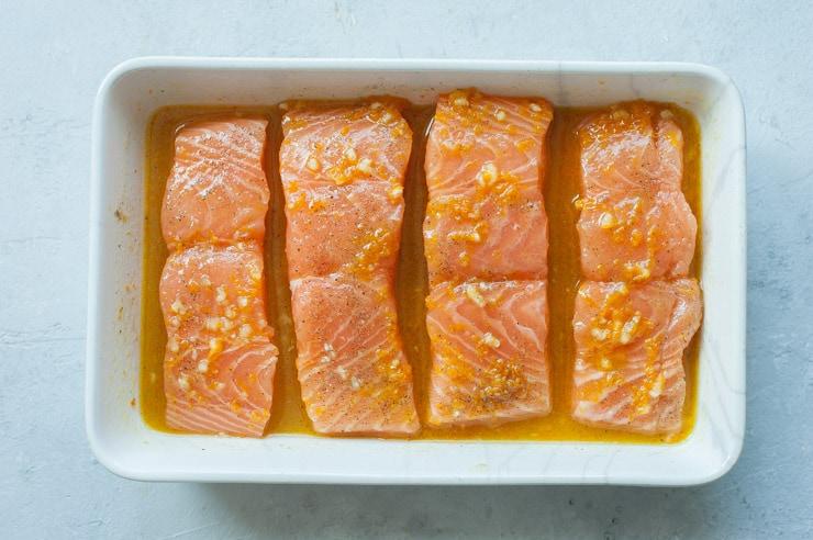 Surowe filety z łososia w sosie pomarańczowym w białym naczyniu do zapiekania.