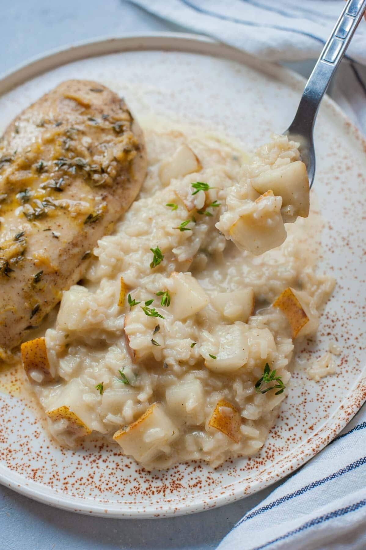 Pear risotto with gorgonzola on a plate with chicken breast on the side.