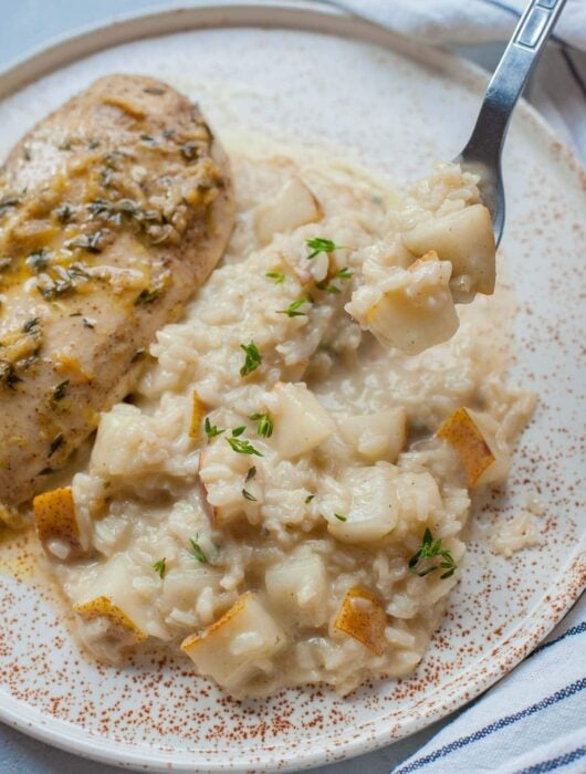 Pear risotto on a white plate with chicken breast on the side.
