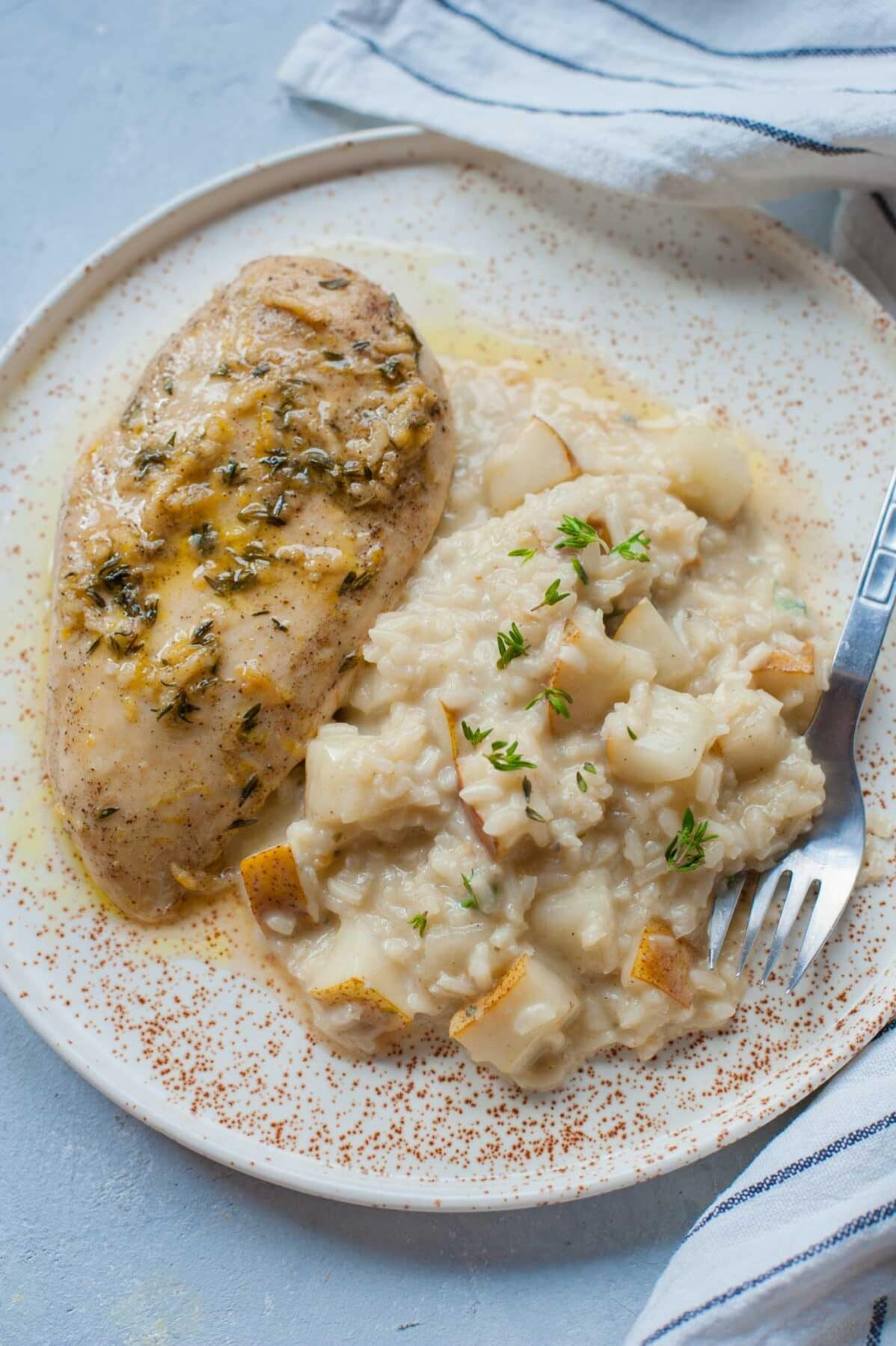 Pear risotto with lemon thyme chicken breast on a white plate.