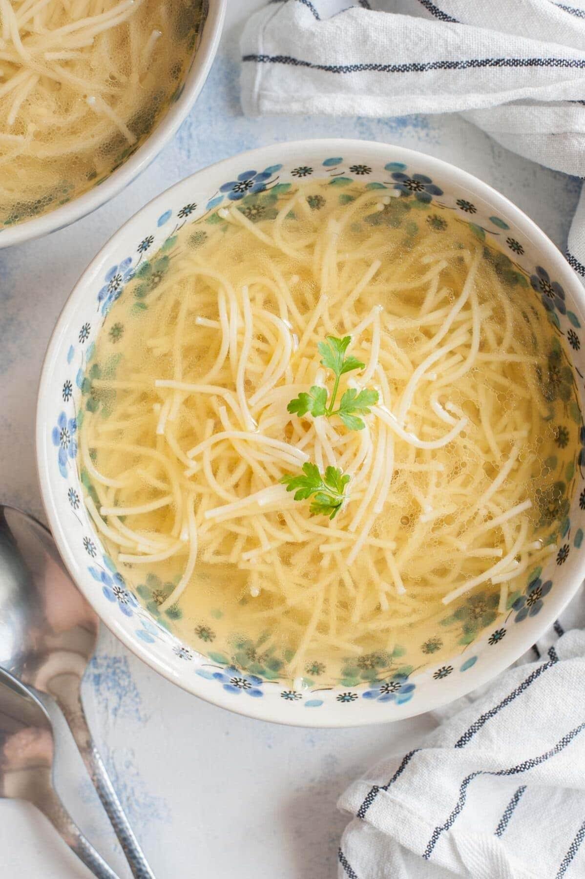 Rosół w biało niebieskiej misce podany z makaronem i pietruszką.