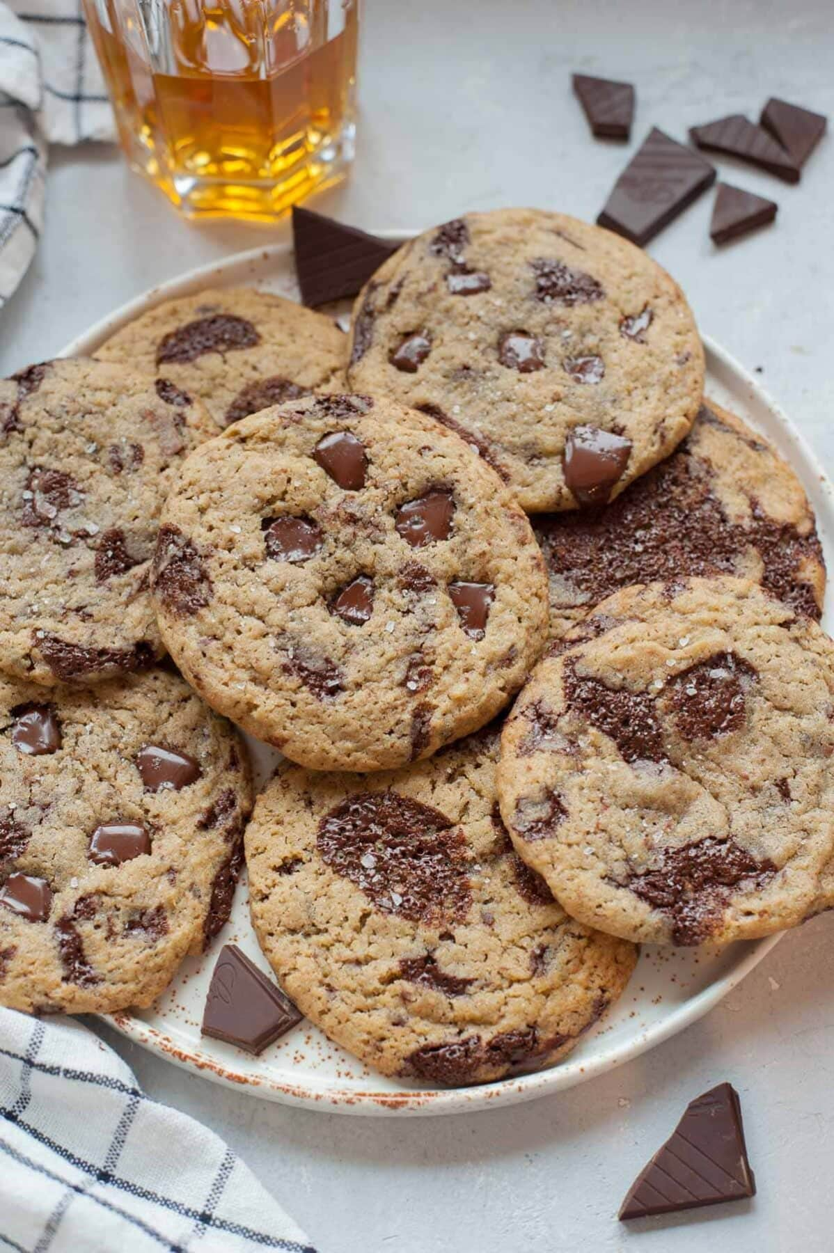Rye chocolate chip cookies on a white plate. A glass with bourbon and chopped chocolate in the background.
