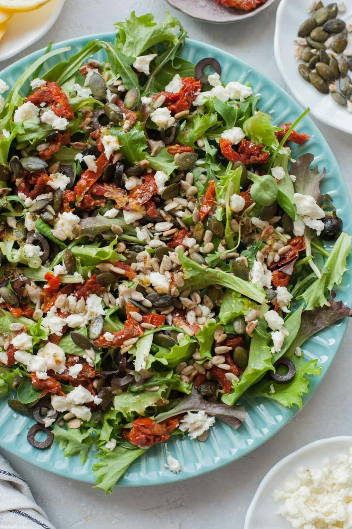 Sun-dried tomatoes salad with olives and feta on a green plate.