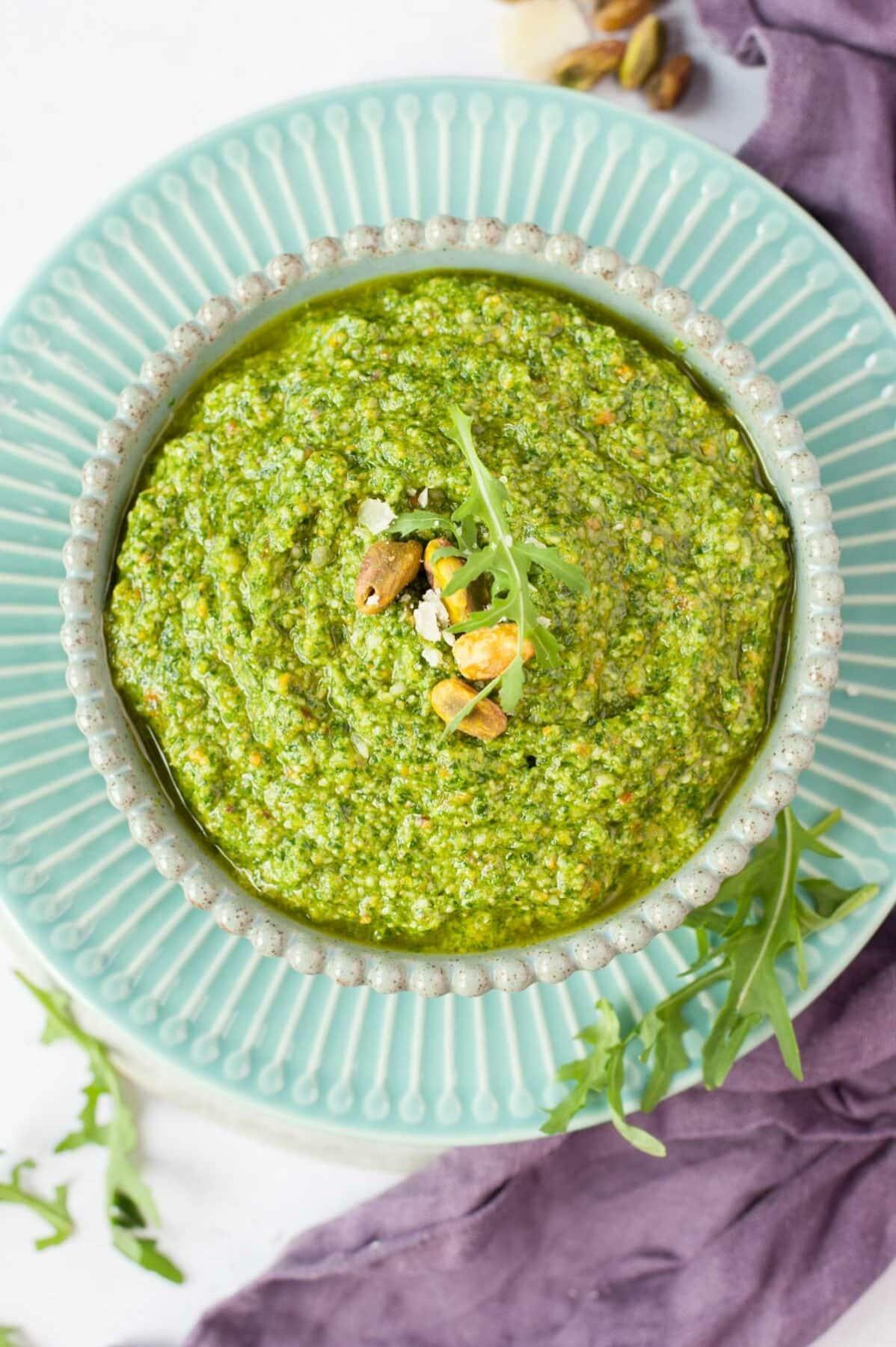 Pesto z rukoli w zielonej misce, na wierzchu liście rukoli i pistacje.