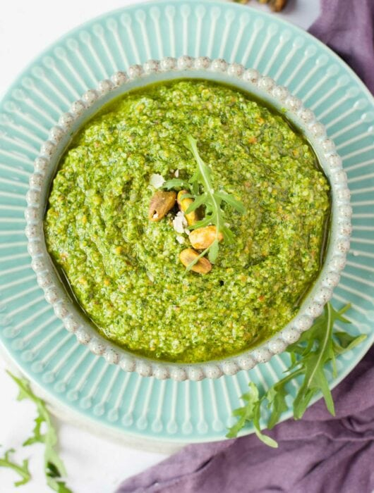 Arugula pistachio pesto in a green bowl.