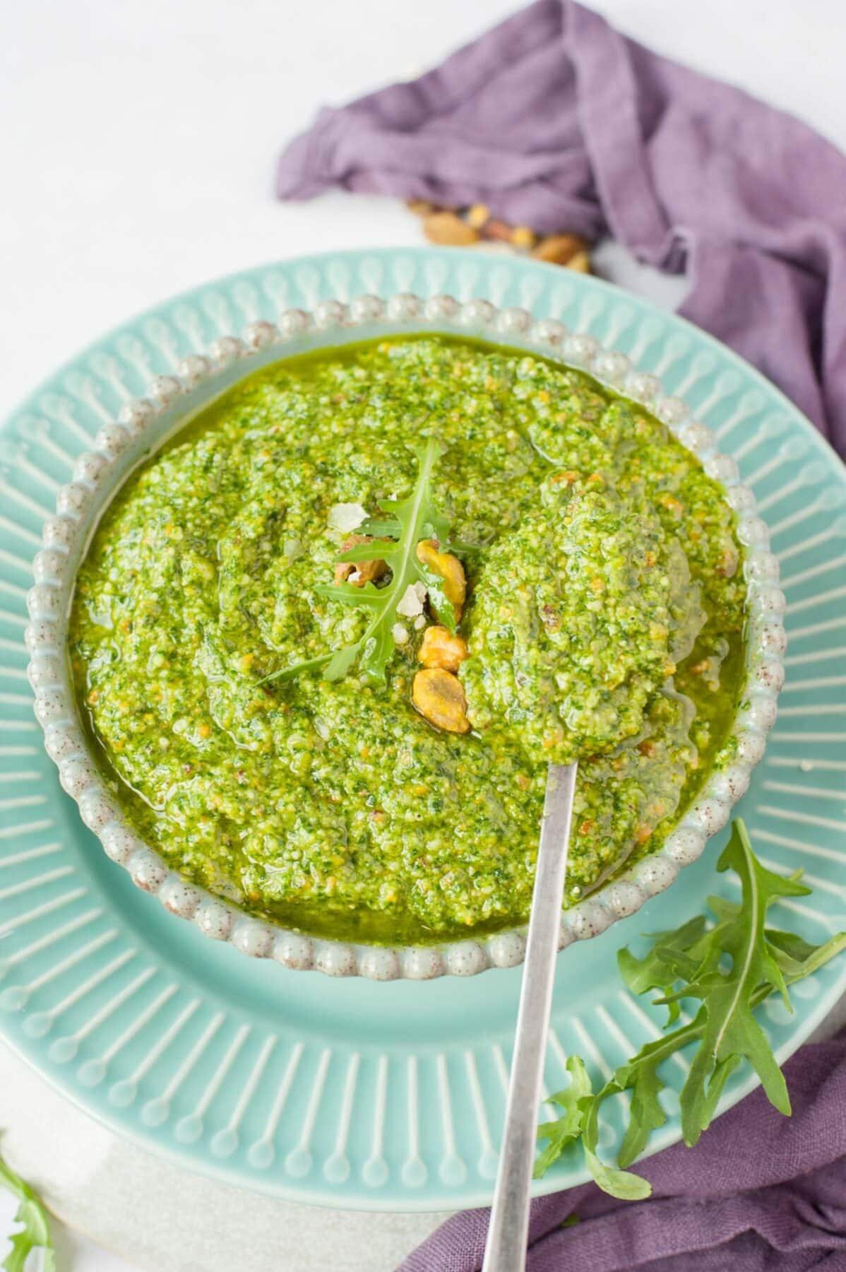 Pesto z rukoli z zielonej misce nabierane na łyżkę.