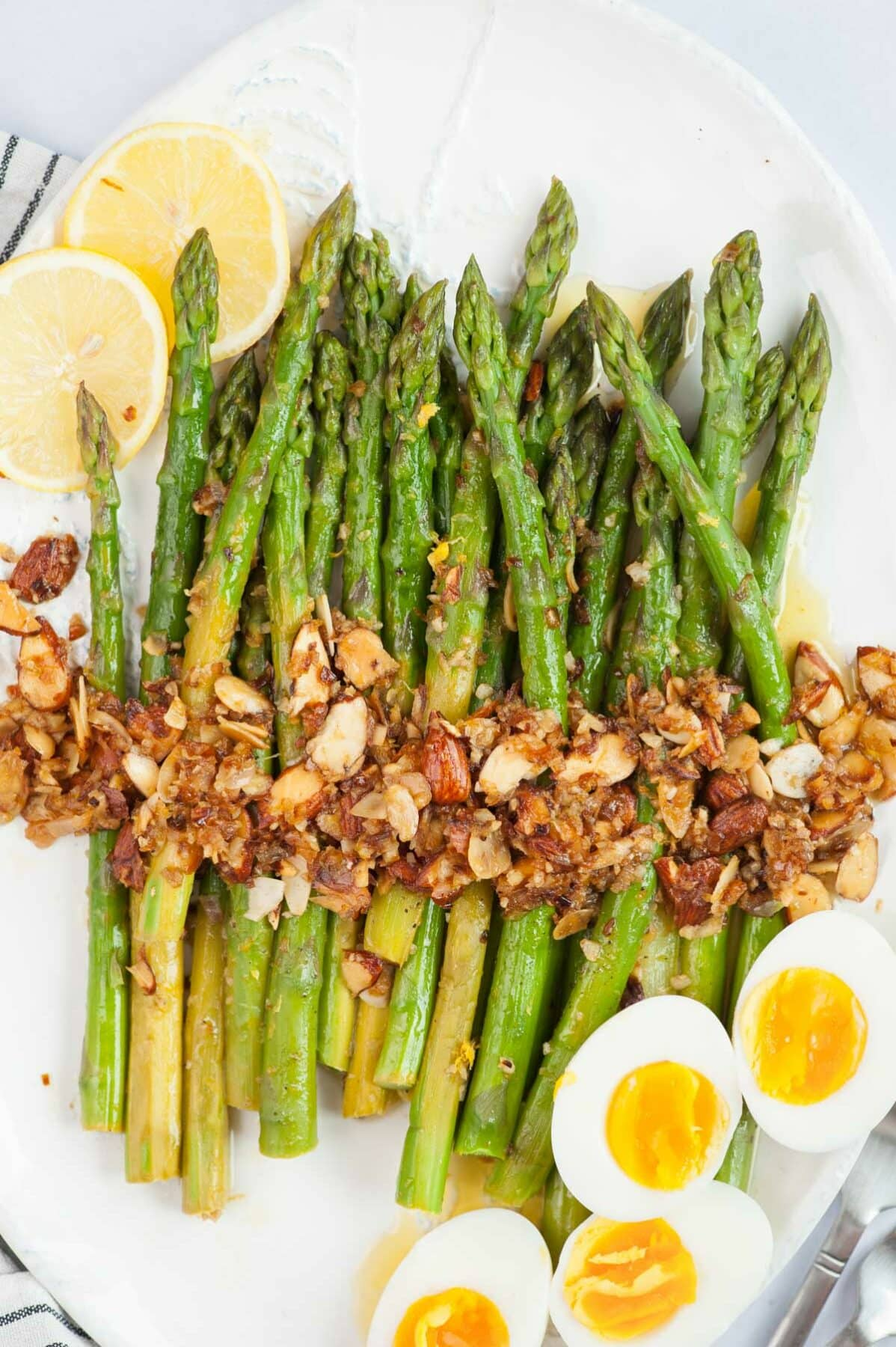 Asparagus almondine on a white plate with lemon slices and halved eggs on the side.