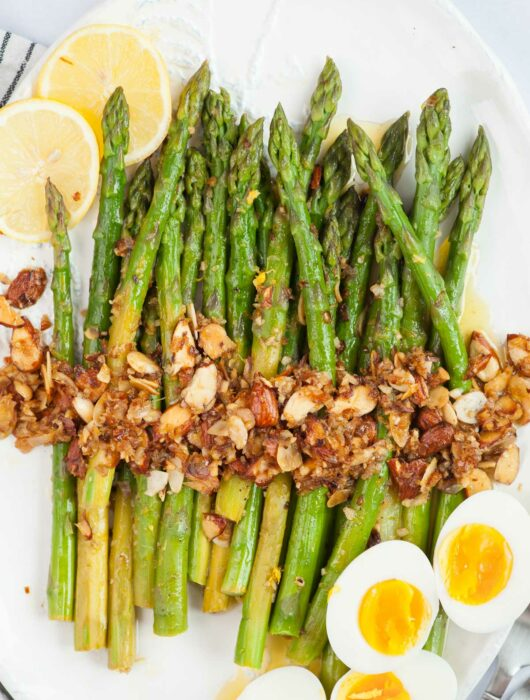 Asparagus almondine topped with almonds garlic. Hard-boiled eggs and lemon slices on the side.