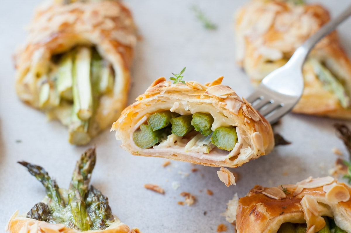 Asparagus in puff pastry with ham and cheese cut in half.
