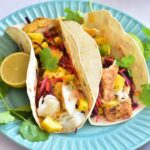 Fish tacos with mango salsa on a blue plate.