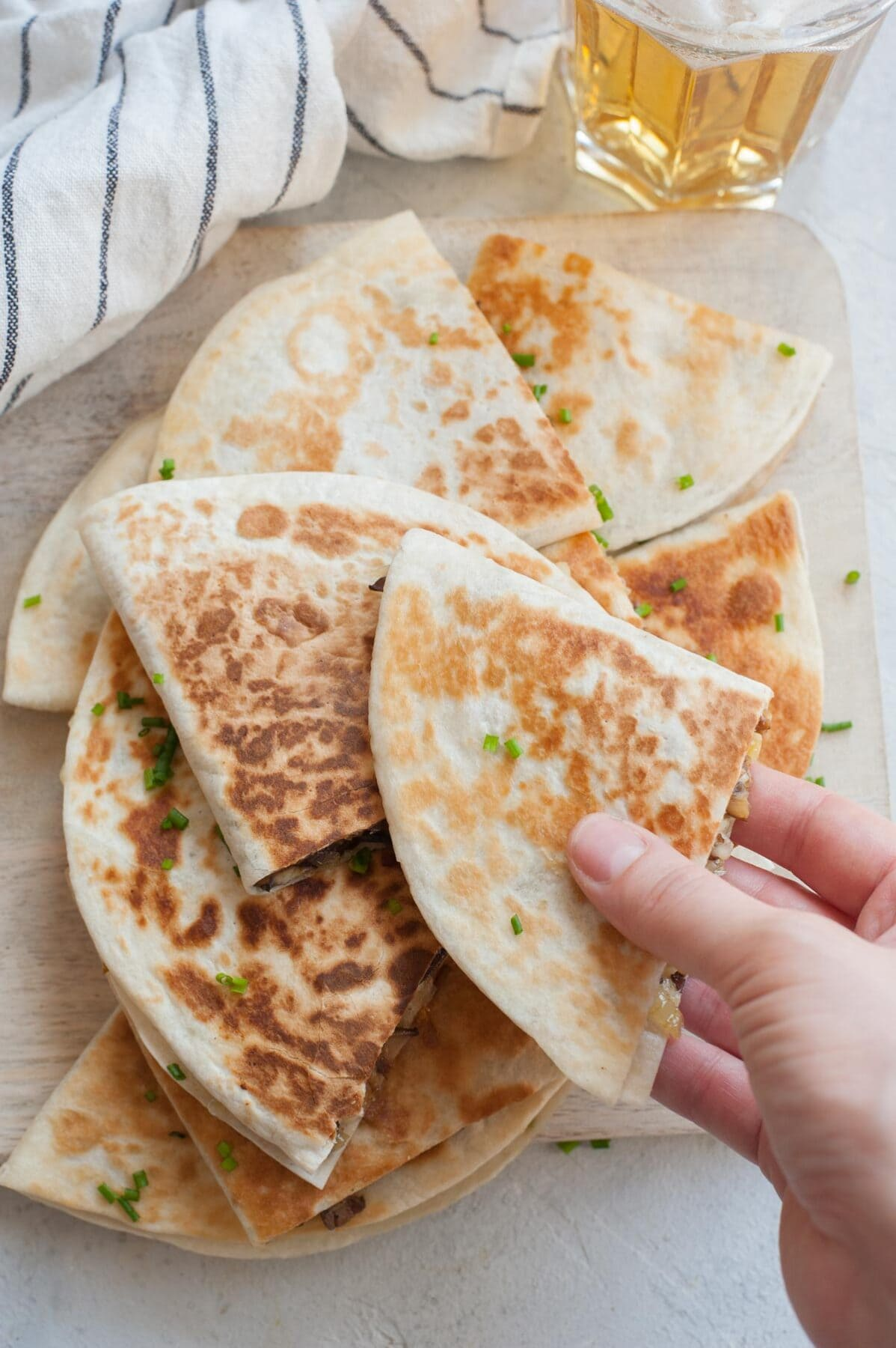 A hand is reaching for a quesadilla. Stack of quesadillas on a wooden board.