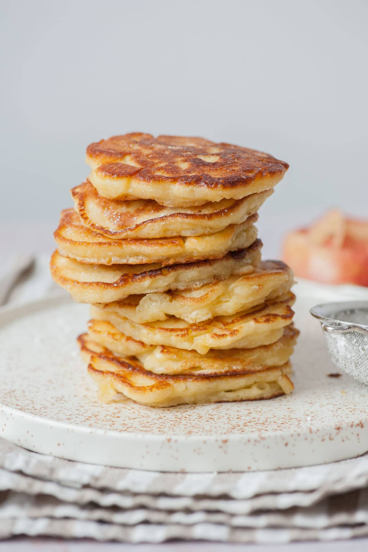 A stack of apple pancakes on a white plate.
