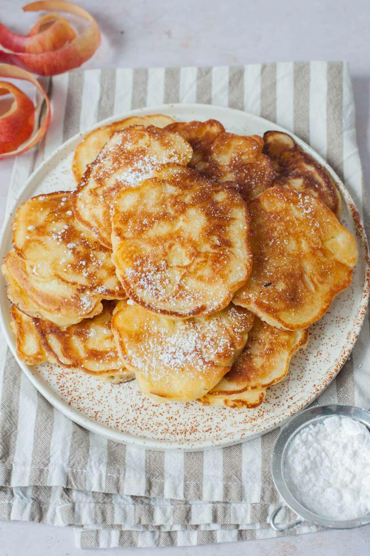 Polish apple pancakes dusted with powdered sugar on a white plate.