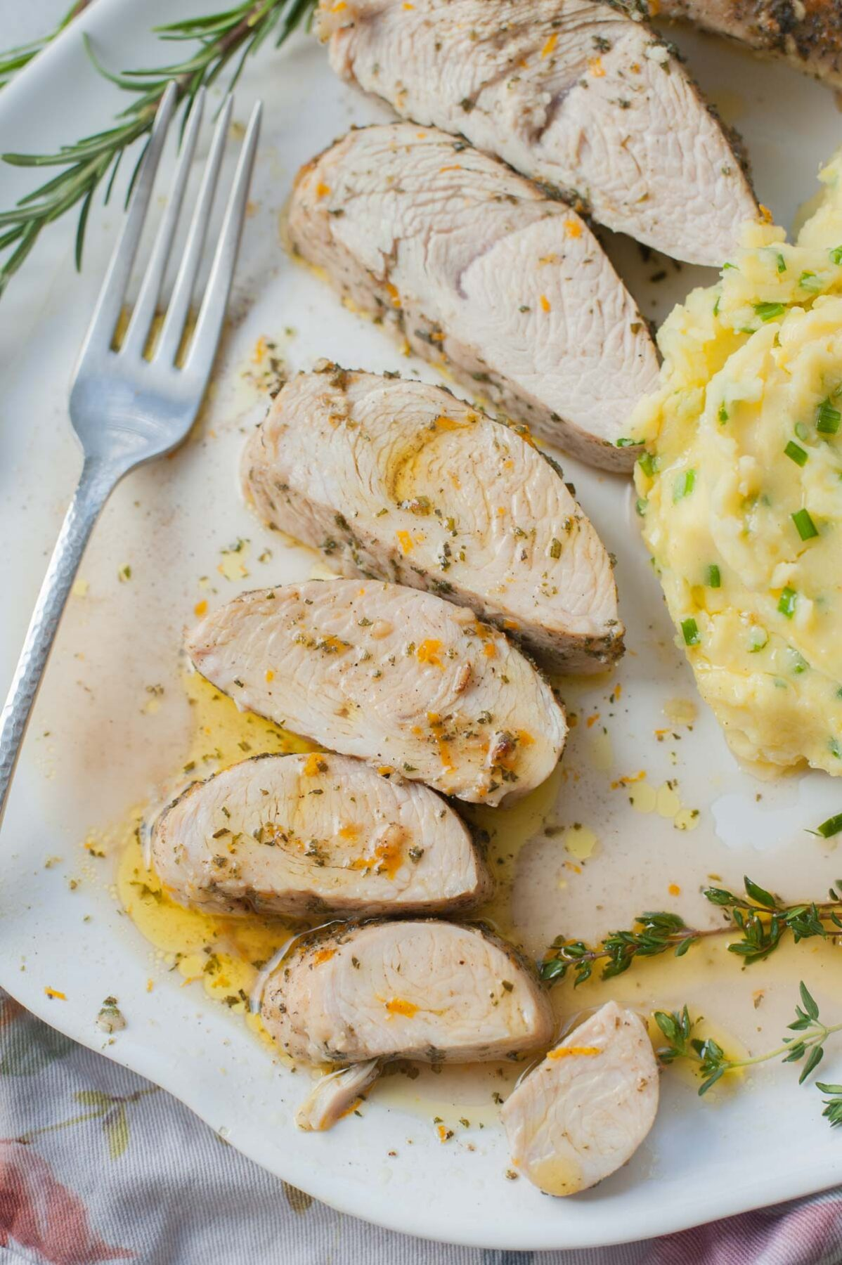 Slices of baked turkey tenderloin on a white plate. Mashed potatoes and fresh herbs on the side.