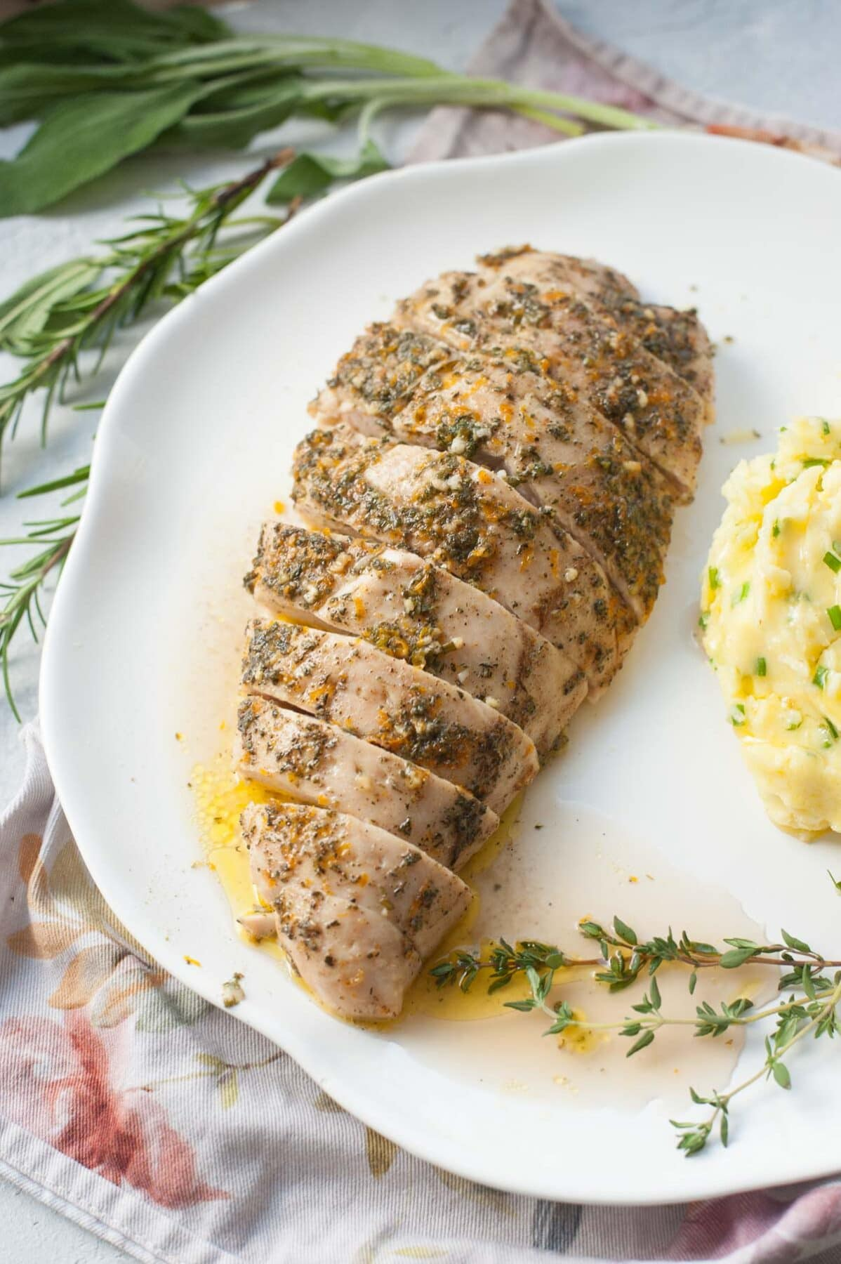 Baked turkey tenderloin cut into slices on a white plate. Herbs in the background.