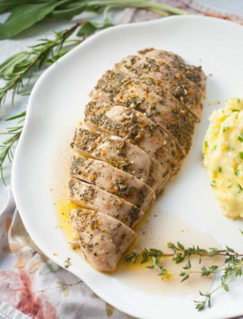 Baked turkey tenderloin on a white plate. Mashed potatoes and fresh herbs in the background.