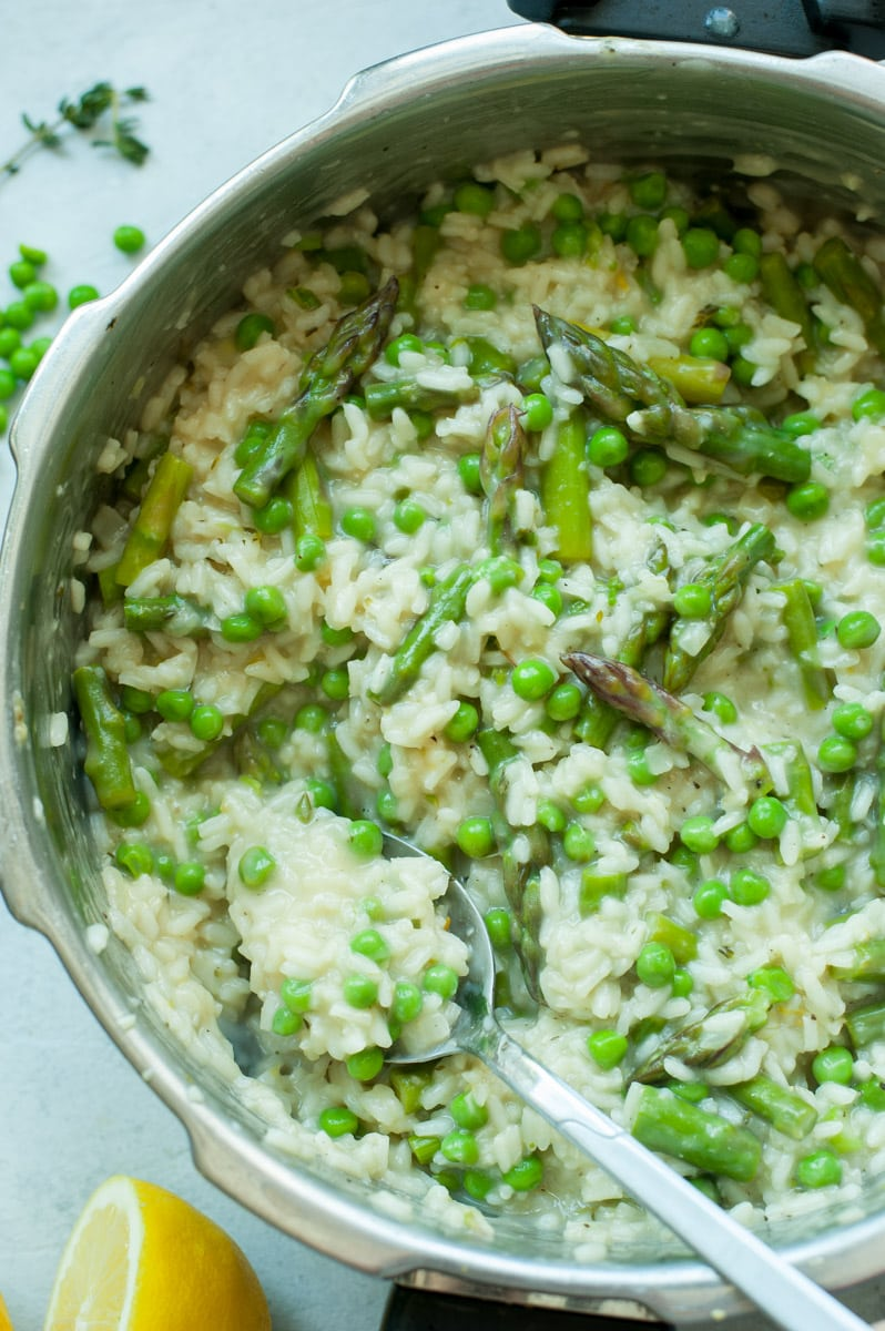Asparagus risotto with peas in a pot with peas and lemons in the background.