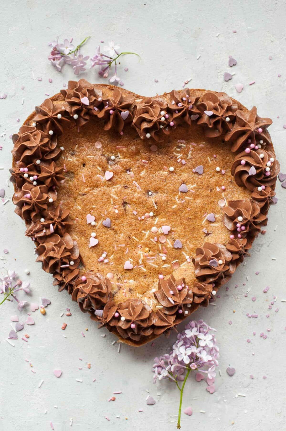 Ciasto z czekoladą i kremem czekoladowym w kształcie serca na szarym tle.