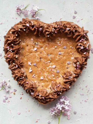Heart-shaped chocolate chip cookie cake on a grey background.