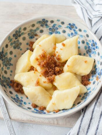 Kopytka with buttered breadcrumbs in a white-blue bowl.