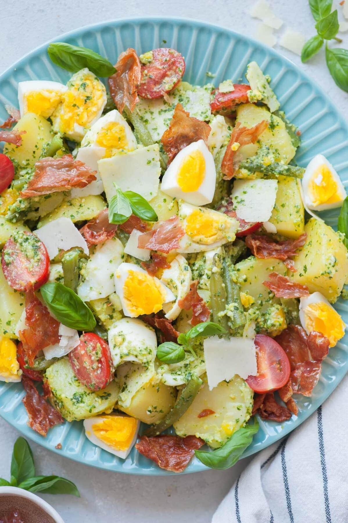 Sałatka ziemniaczana z pesto, jajkami i fasolką szparagową, pomidorkami cherry i szynką prosciutto na niebieskim talerzu.