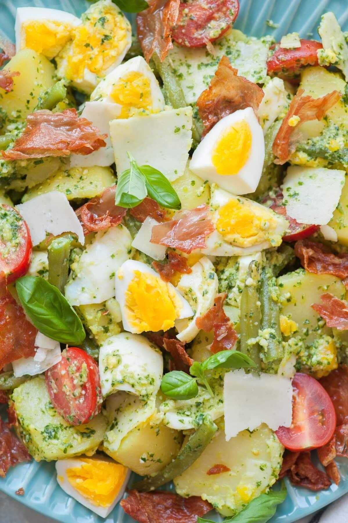 Sałatka ziemniaczana z pesto, jajkami i fasolką szparagową, pomidorkami cherry i szynką prosciutto.