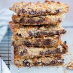A stack of 7-layer magic bars on a piece of parchment paper.