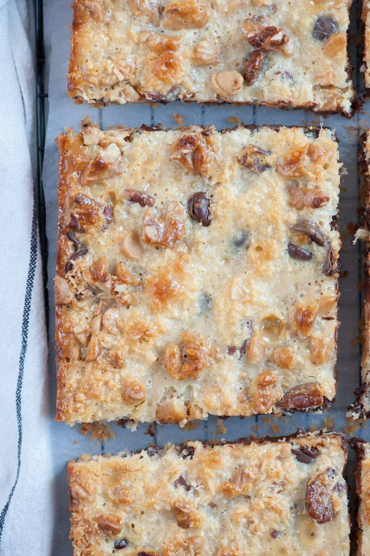 A close up photo of 7-layer magic bars on a cooling rack.