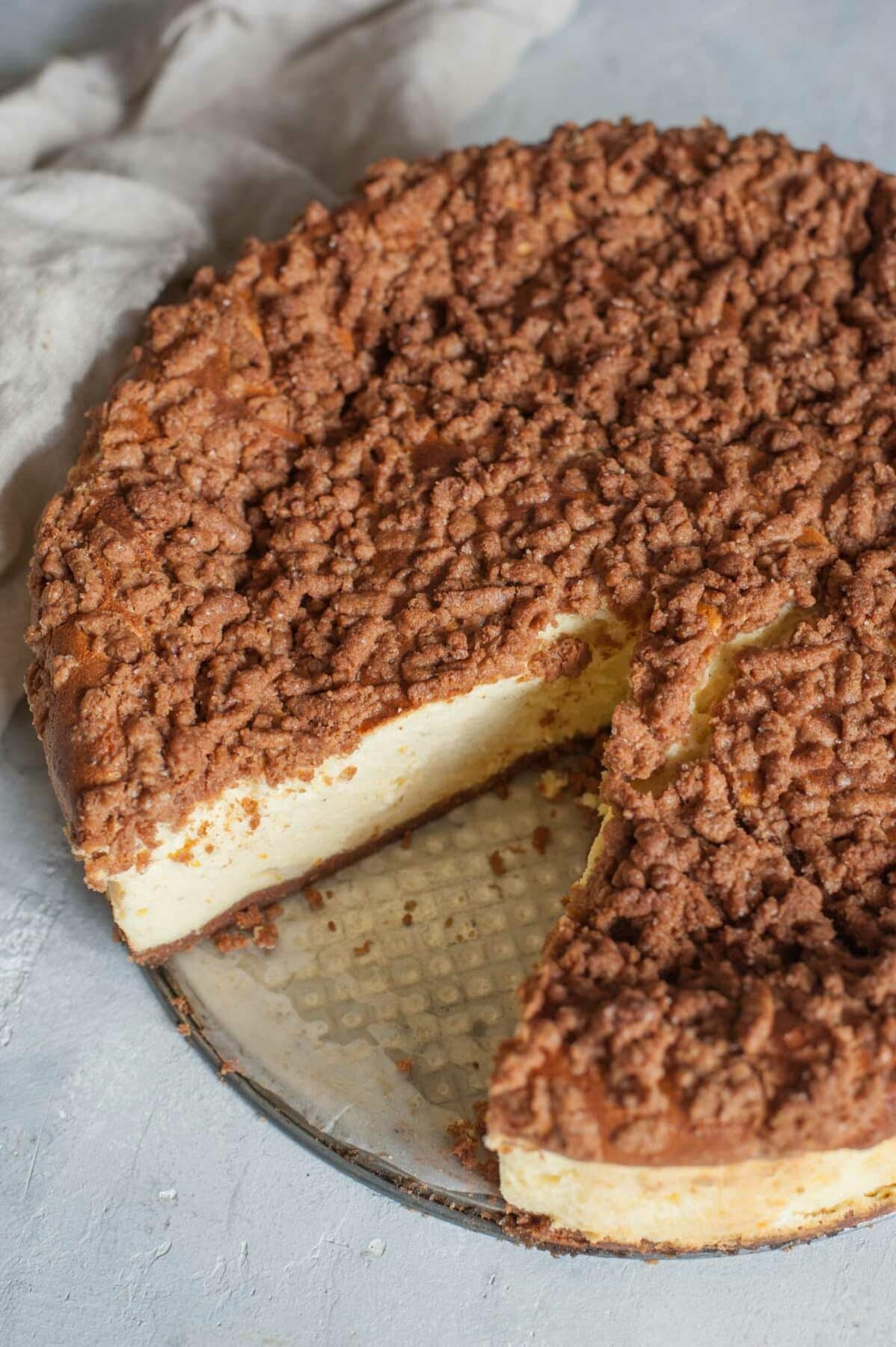 Polish cheesecake with a piece missing on a table.