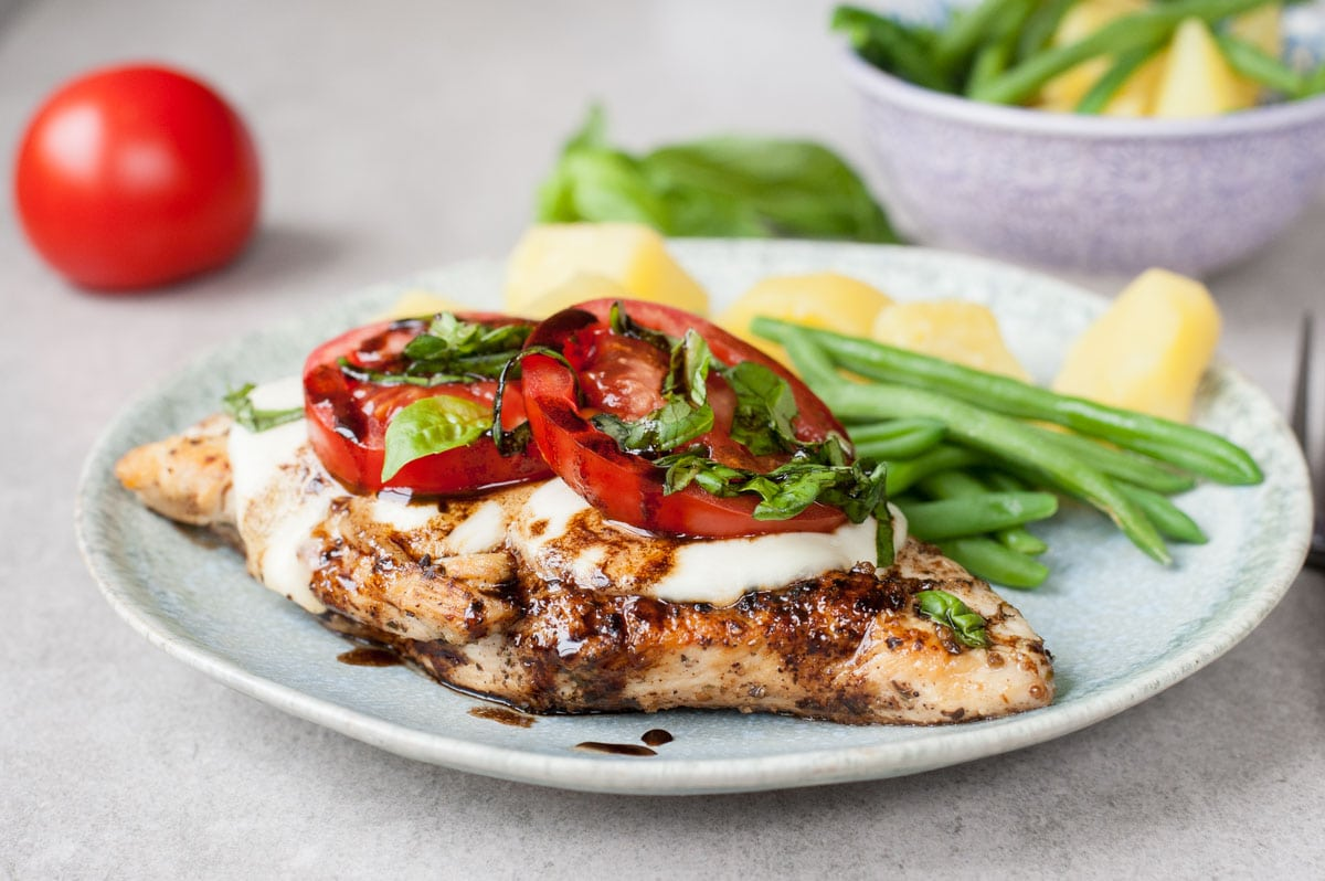 Caprese chicken with mozzarella, tomatoes and basil on a green plate with a side of green beans and potatoes.