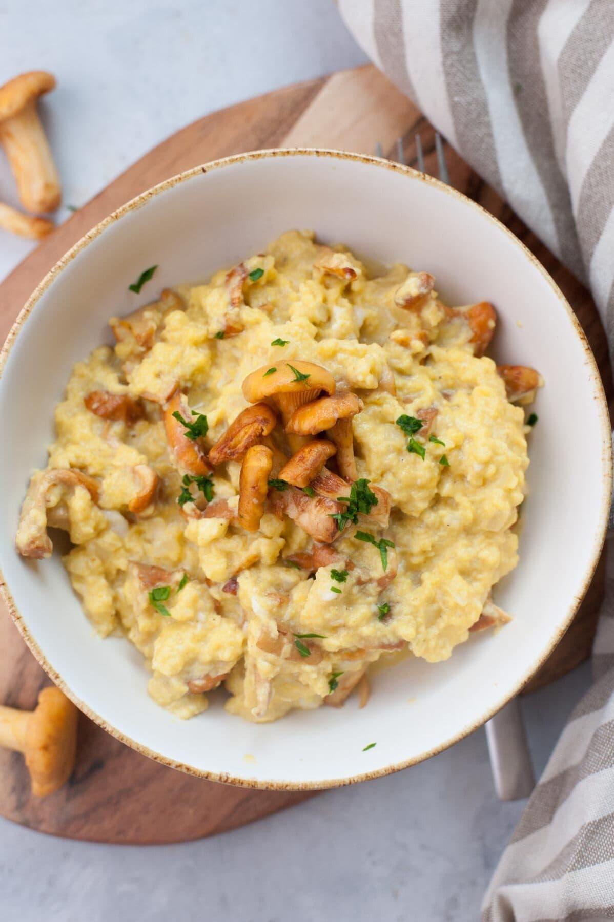 Chanterelle scrambled eggs in a white bowl.