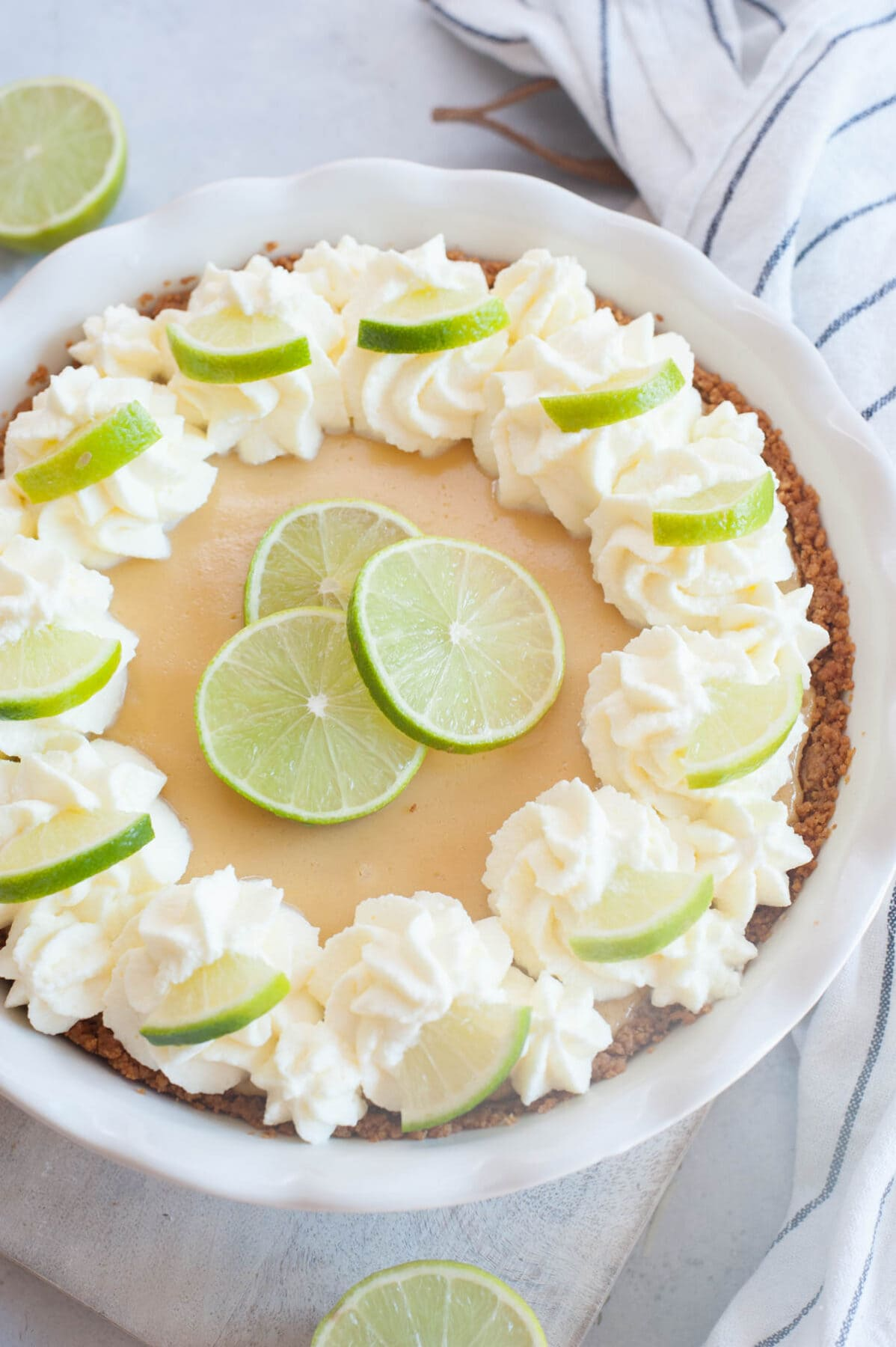 Key lime pie in a pie dish topped with whipped cream and lime slices.