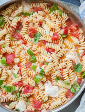 Hot Caprese pasta in a frying pan.