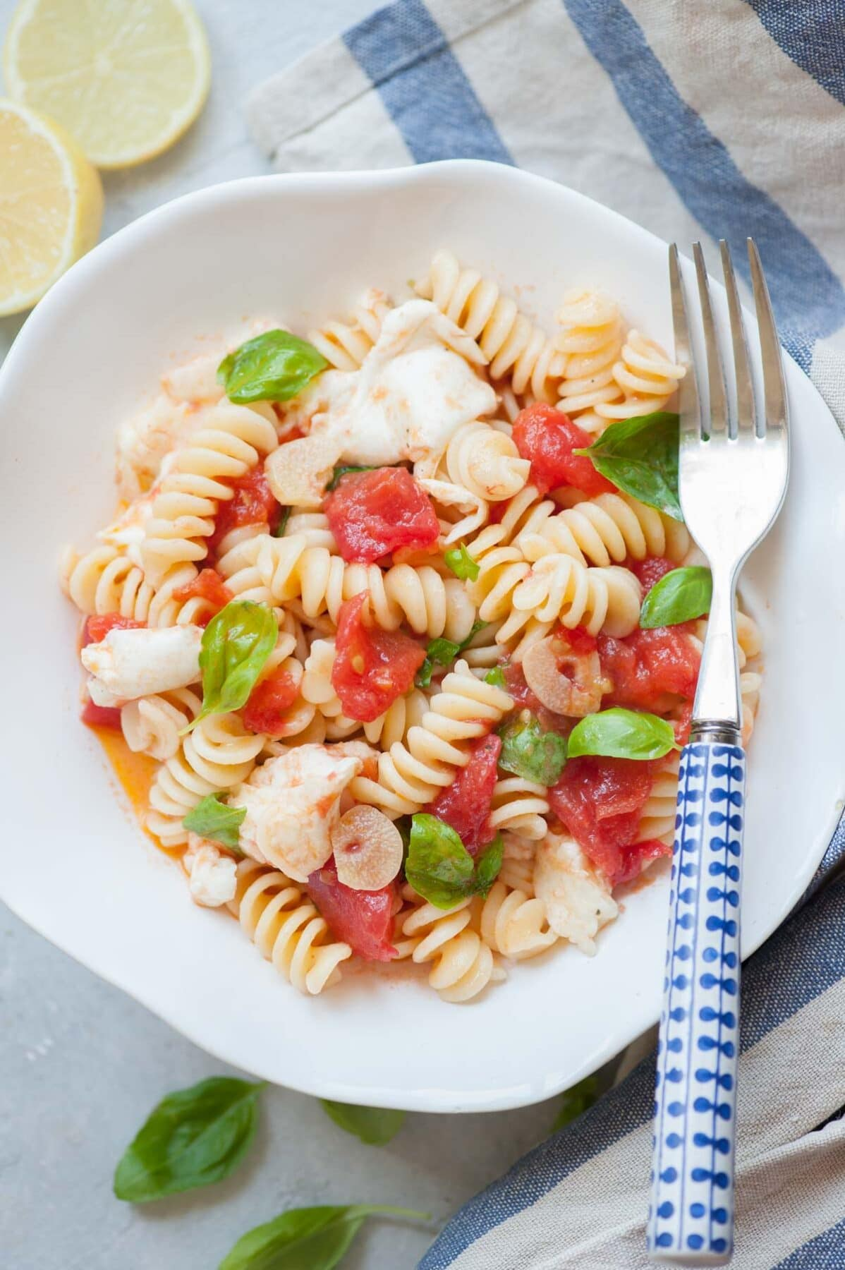 Pasta Caprese in a white bowl with blue fork on the side.