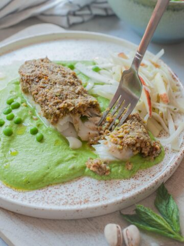Pistachio crusted fish with mint puree and kohlrabi slaw on a white plate.