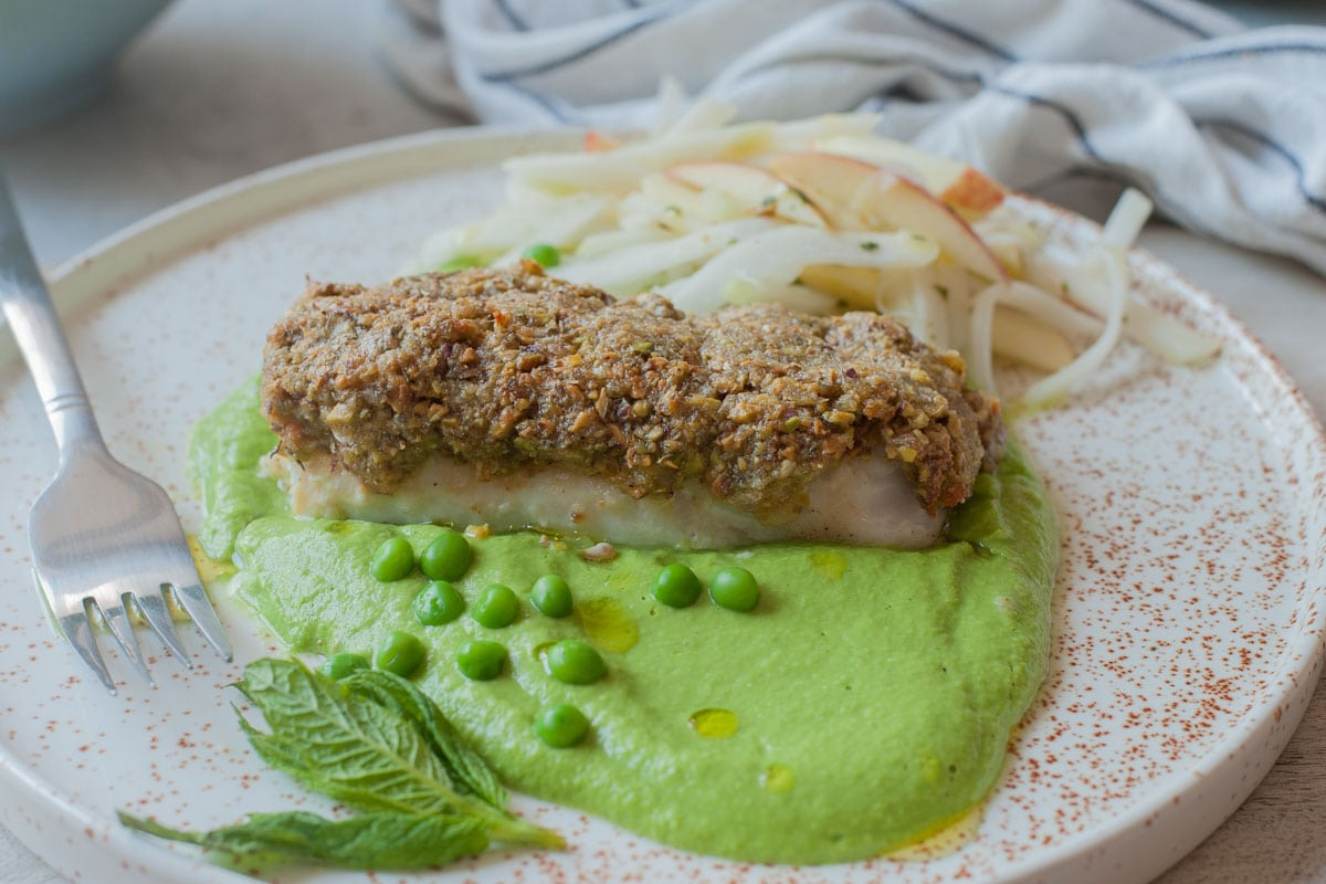 A horizontal picture of pistachio crusted fish with pea puree and kohlrabi slaw on a white plate.