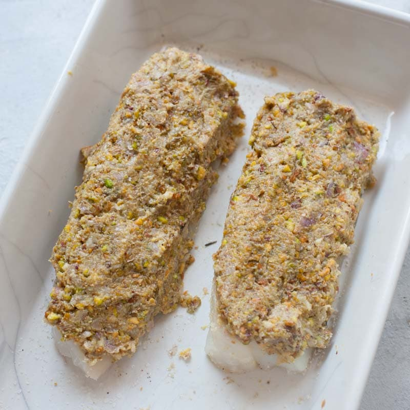 Cod fillets in a white baking dish ready to be baked topped with pistachio mixture.