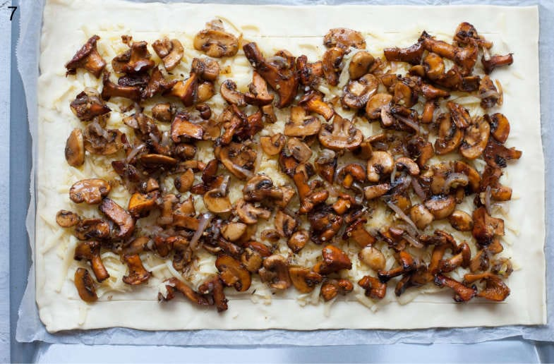 Sautéed mushrooms, onions, and shredded cheese on a puff pastry sheet.