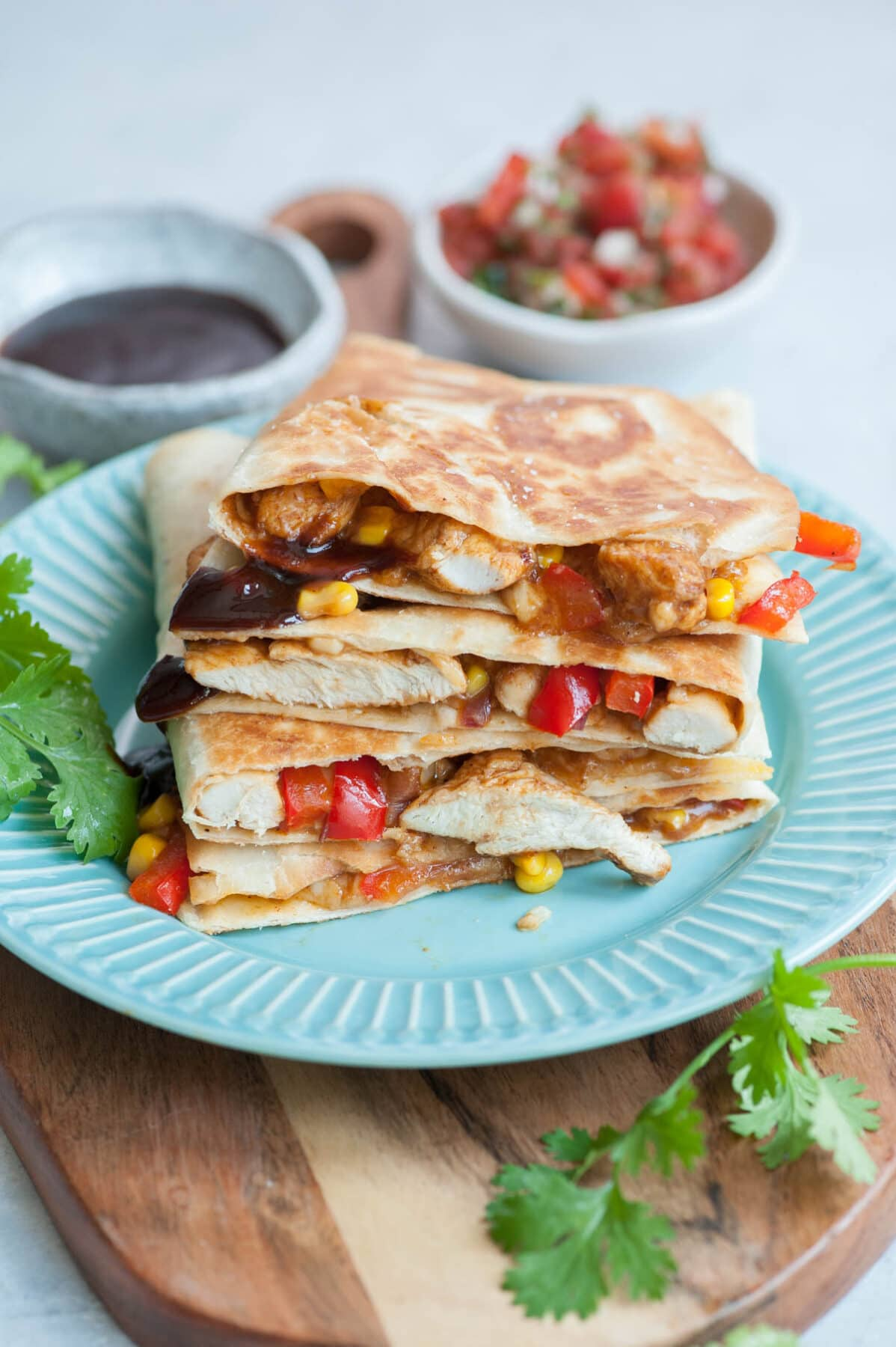 A stack of BBQ Chicken Quesadillas on a blue plate.