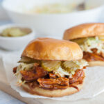 Bbq pulled chicken sandwich on a piece of parchment paper on a wooden board.