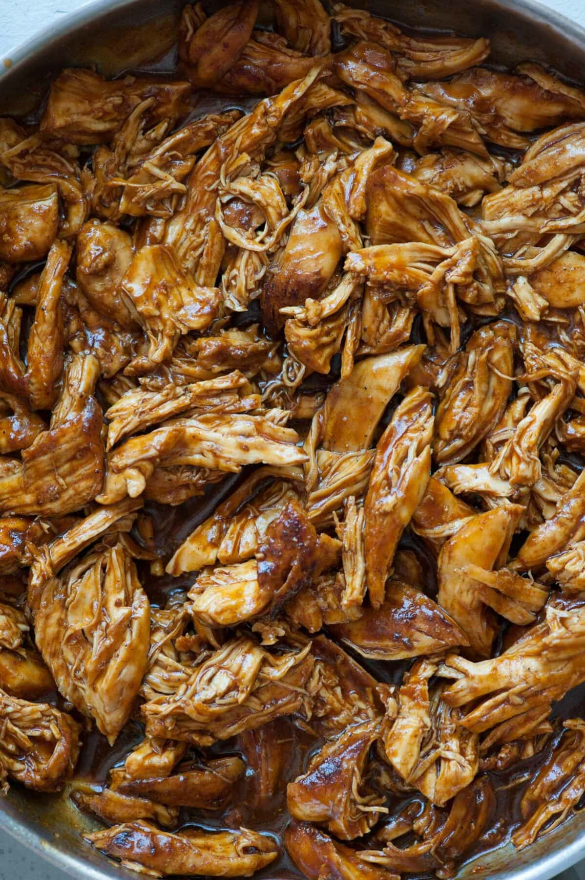 A close up photo of bbq pulled chicken in a pan.