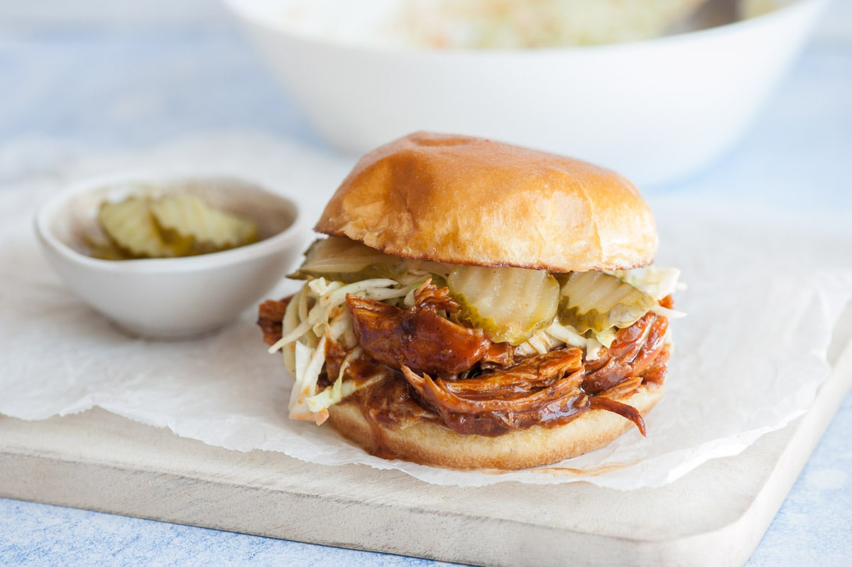 BBQ Pulled Chicken Sandwich on a piece of parchment paper on a white wooden board. Pickles in the background.