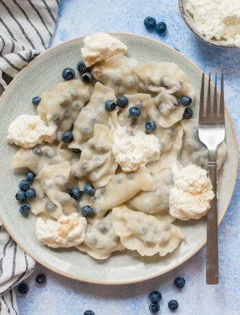 Blueberry pierogi served with fresh blueberries and whipped cream on a blue plate.
