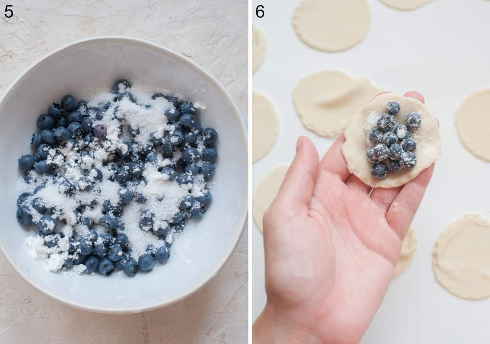 Blueberries with flour and sugar in a bowl. Pierogi dough round with blueberries on top is being held in a hand.